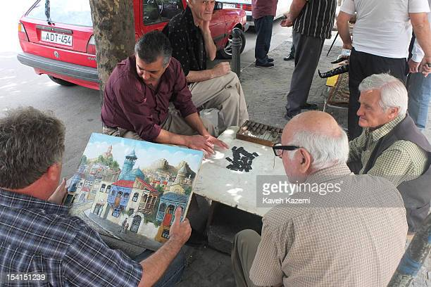 A man holds a painting of old city going for sale while others play a board game while sat in the flea market on June 10 2012 in Tbilisil Georgia