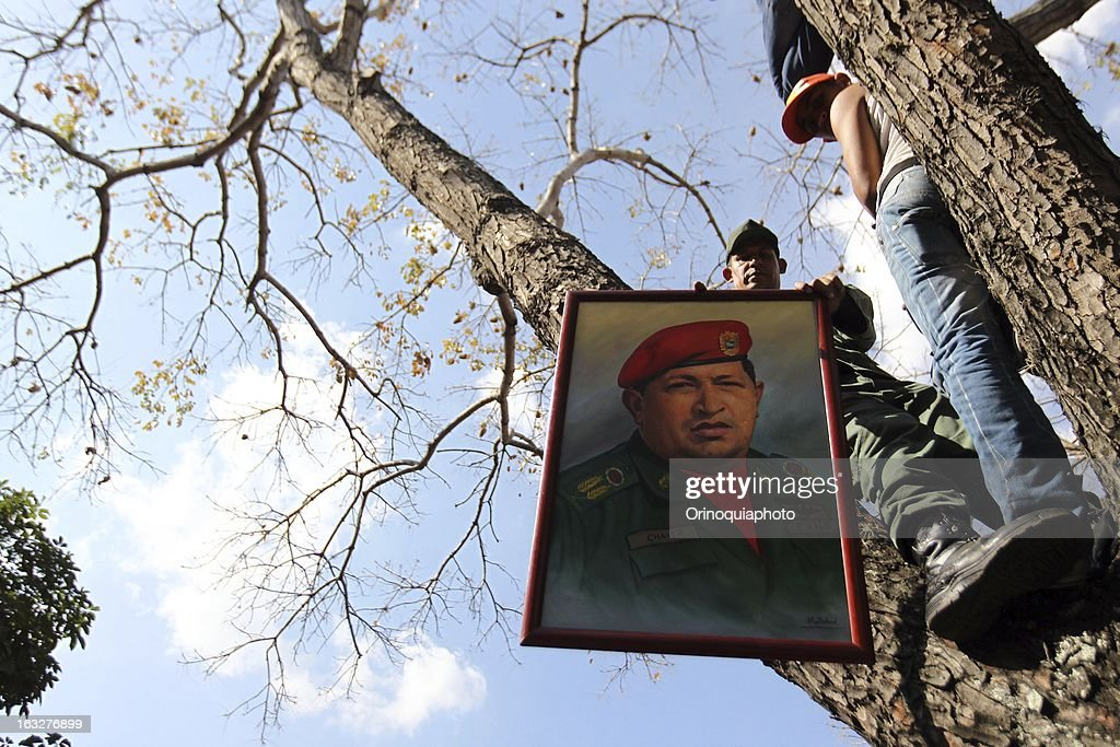 A man holds a photo of Hugo Chavez during the march of the supporters of President Hugo Chavez through the streets of Caracas to the military academy on March 06, 2013 in Caracas, Venezuela.