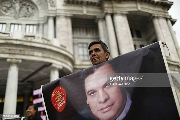 A man holds a photo of the late Mexican singersongwriter in front of the Fine Arts Palace in Mexico City on September 4 2016 while waiting for the...