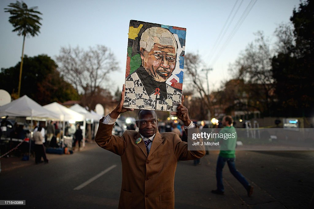 A man holds a picture as people gather to leave messages of support for former South African President Nelson Mandela outside the Mediclinic Heart Hospital June 26, 2013 in Pretoria, South Africa. South African President Jacob Zuma confirmed on June 23 that Mandela's condition has become critical since he was admitted to the hospital over two weeks ago for a recurring lung infection.