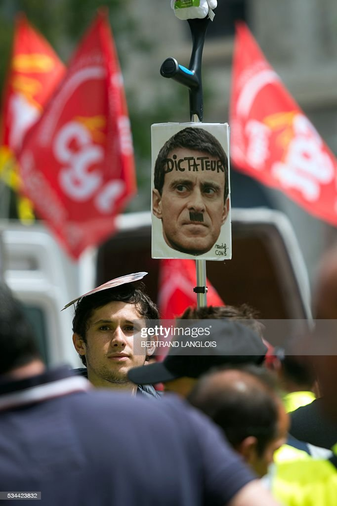 A man holds a picture of Manuel Valls during a demonstration against the French government's planned labour law reforms in front of Les Terrasses du Port commercial centre on May 26, 2016 in Marseille. The French government's labour market proposals, which are designed to make it easier for companies to hire and fire, have sparked a series of nationwide protests and strikes over the past three months. / AFP / BERTRAND