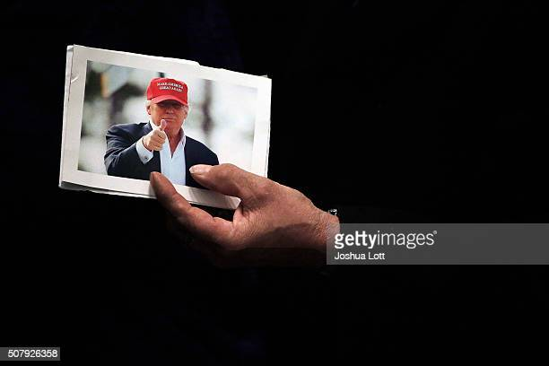 A man holds a picture of Republican presidential candidate Donald Trump at the rope line during a campaign event at the US Cellular Convention Center...