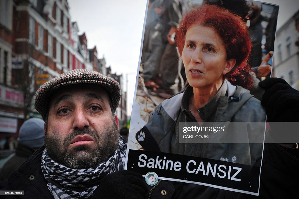 A man holds a picture of Sakine Cansiz, one of three top Kurdish activists from a separatist group banned in Turkey who were killed earlier this week in France, during a rally demanding them justice in north London on January 13, 2013. The three activists -- Sakine Cansiz, Fidan Dogan and Leyla Soylemez -- were found dead on January 10 at the Kurdistan Information Centre in the grimy 10th district of Paris, after last being seen alive at the centre at midday on January 9.