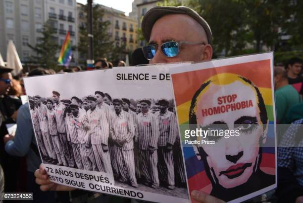 A man holds a picture of Vladimir Putin as he takes part in a protest in Madrid against the persecution of gay men in Chechnya