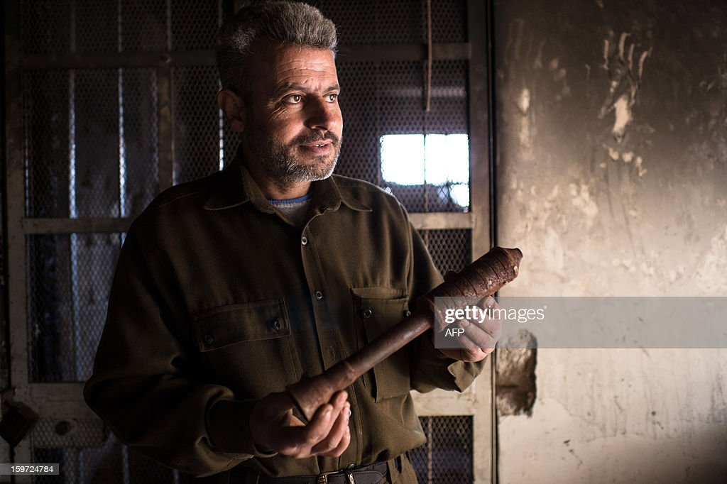 A man holds a piece of a hand made missile that he produces in a secret factory on January 19, 2013 in Al-Bab, 30 kilometers from the northeastern Syrian city of Aleppo. Recycled or non explosed bombs recolted after shellings are used for the manufacturing and sugar as well for the propulsion. Each day, nearly 50 missiles are assembled for the Abu baker Brigade.