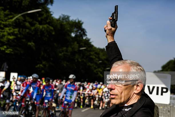 A man holds a pistol to give the start sign while participants wait for the start to ride a bike part at the 8th Garmin Velothon on May 31 2015 in...