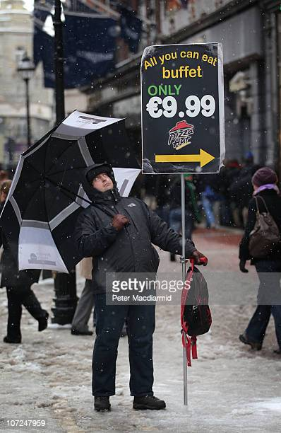 A man holds a placard advertising low cost meals in Grafton Street on December 2 2010 in Dublin Ireland The Irish economy has faltered after years of...