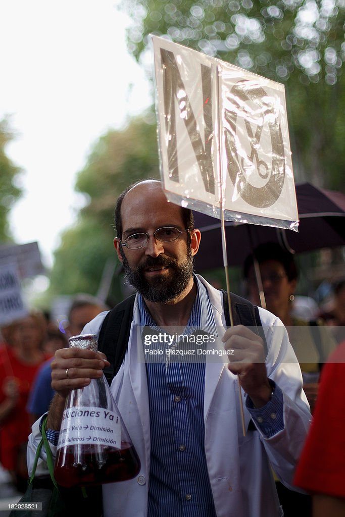 A man holds a placard and a test tube during a demonstration with other researchers against R&D cuts for sciences on September 27, 2013 in Madrid, Spain. Young Spanish scientists have called for a demonstration during the European Researchers' Night under the header, 'No Sciences, No Future', in response to cutbacks in research and development for Sciences. They claim that many Spanish researchers are leaving the country to find a jobs.
