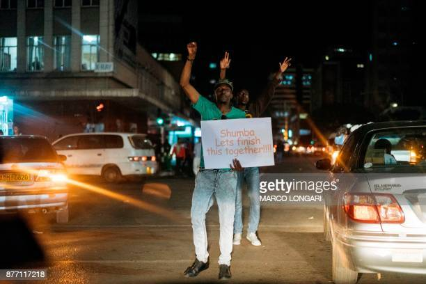 A man holds a placard as he celebrates with others Zimbabweans in the street of Harare after the resignation of President Mugabe on November 21 2017...
