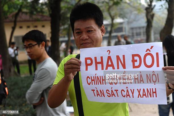 A man holds a placard as he joins a rally protesting against a treefelling plan by the municipal authorities in Hanoi on March 22 2015 Vietnam...