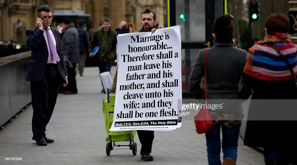 A man holds a placard bearing a passage from the bible as he makes a protest against legislation allowing gay marriage as he walks past Parliament ahead of the gay marriage vote in London on February 5, 2013. Opponents of British Prime Minister David Cameron's bid to push through legislation allowing gay marriage attacked the bill ahead of a vote in parliament later. Cameron has championed the drive to allow same-sex couples to marry in England and Wales but faces the embarrassing prospect of seeing half his party's lawmakers opposing him in the vote which has created bitter divisions. AFP PHOTO/ANDREW COWIE