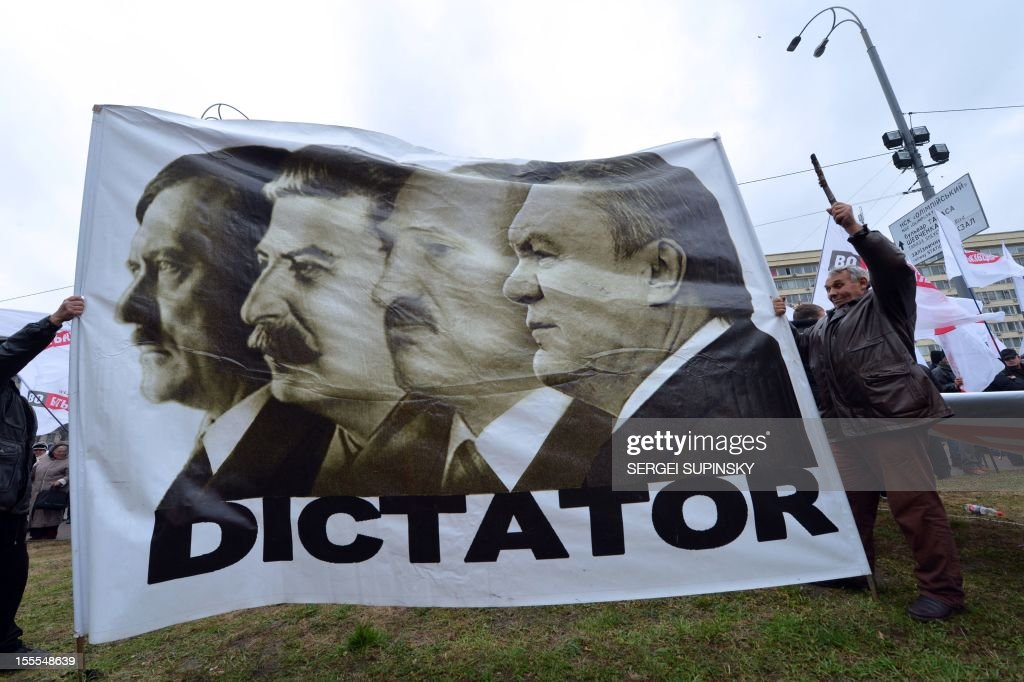 A man holds a placard depicting Adolf Hitler, Josef Stalin, Belarus President Alexander Lukashenko and Ukrainian President Viktor Yanukovych and reading'Dictator' during a rally of the opposition in front of the central election commission in Kiev on November 5, 2012. Thousands of Ukrainians massed in central Kiev on November 5 to protest against alleged fraud in parliamentary elections won by the ruling party as the opposition threatened not to recognise the new legislature. At least 2,000 opposition supporters carrying Ukrainian flags gathered outside the headquarters of the central election commission amid a heavy presence of elite Berkut anti-riot police, an AFP correspondent said.