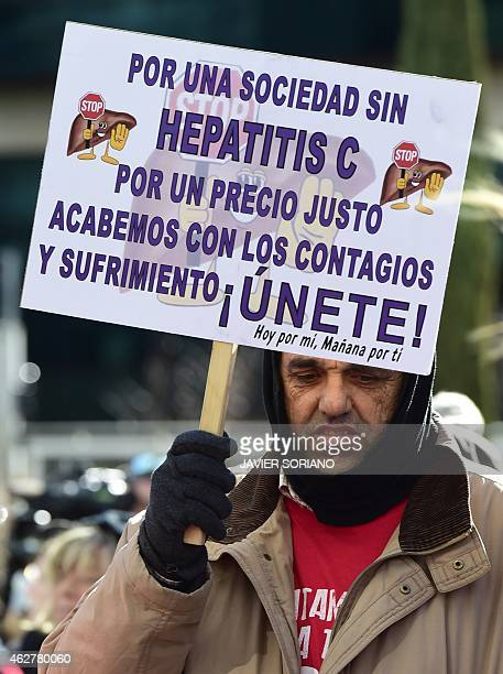 A man holds a placard during a demonstration by Hepatitis C sufferers and supporters outside US laboratory Gilead Sciences office in Madrid on...