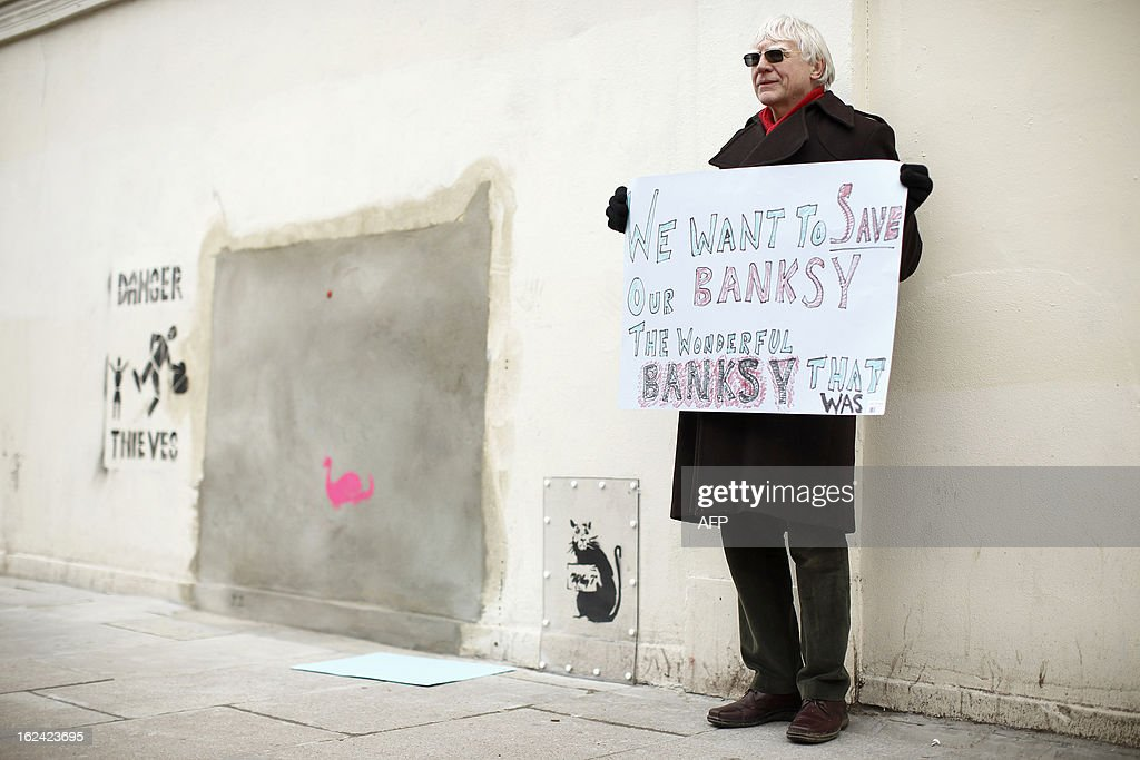 A man holds a placard during a protest next to a section of a wall where celebrated street artist Banksy's 'Slave Labour' graffiti artwork was removed in north London on February 23, 2013. The work that showed a young boy using a sewing machine to make the British flag has been carefully removed and will be auctioned in Miami where it's expected to fetch around 328,000 GBP (500,000 USD). Residents of the North London area have reacted angrily to the removal of the work, but the auction house says the piece was acquired legally.