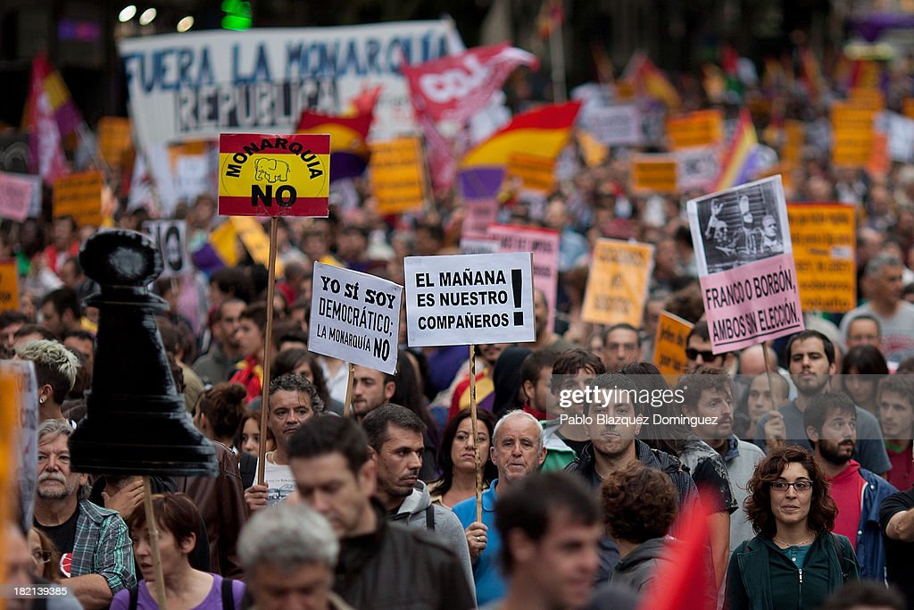 A man holds a placard (L) of a Spanish flag reading 'No Monarchy' during a demonstration against the Spanish Monarchy under the header 'Check the King' at Princesa Street on September 28, 2013 in Madrid, Spain. Organizers call for a demonstration on the anniversary of 'Surround the congress protest' to claim the abolition of the Monarchy. Currently King Juan Carlos of Spain is in hospital recovering from a hip operation. The Spanish Royal Family has lost popularity since the King injured his hip on elephant hunting trip and the King's son-in-law, Inaki Urdangarin is being investigated over a corruption scandal.