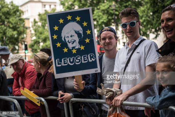 A man holds a placard outside Downing Street following a speech by British Prime Minister Theresa May after the Conservative Party failed to win a...