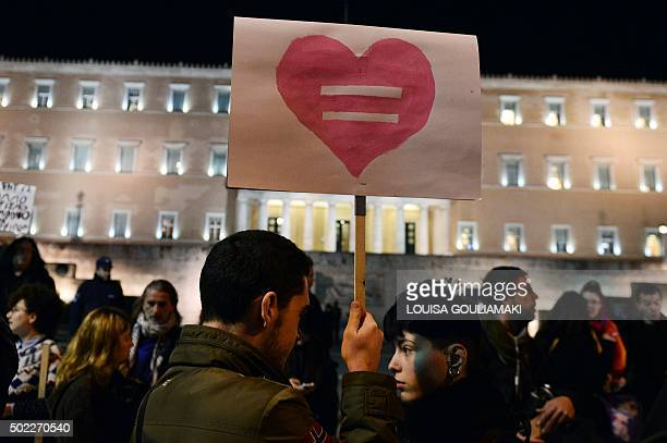 TOPSHOT A man holds a placard picturing an equality sign inside a heart during a demonstration of gay rights activists and members of the Athens LGBT...
