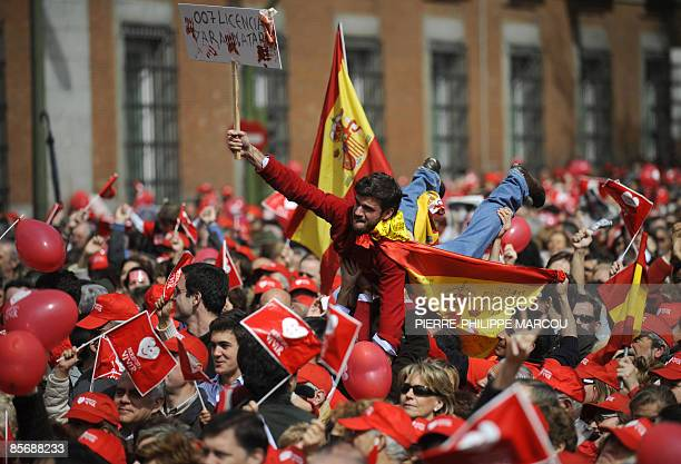 A man holds a placard reading '007 Licence to kill' during a demonstration to protest the government's plans to liberalise the abortion law in Madrid...