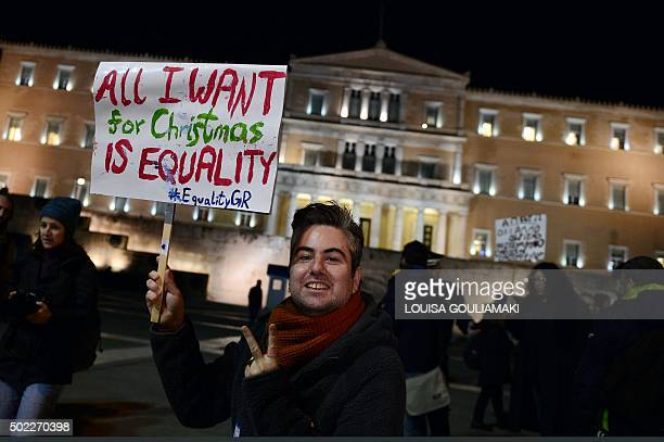 A man holds a placard reading 'All I want for Christmas is equality' during a demonstration of gay rights activists and members of the Athens LGBT...