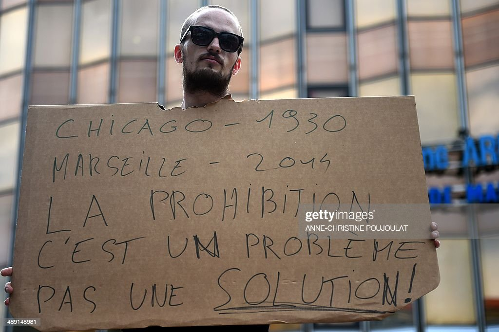 A man holds a placard reading 'Chicago - 1930, Marseille - 2014, Prohibition it's a problem not a solution' during a protest to call for the legalization of marijuana on May 10, 2014, in Marseille, southern France. About 147 million people globally -- or about 2.5 percent of the population -- use cannabis, according to the World Health Organization. AFP PHOTO / ANNE-CHRISTINE POUJOULAT