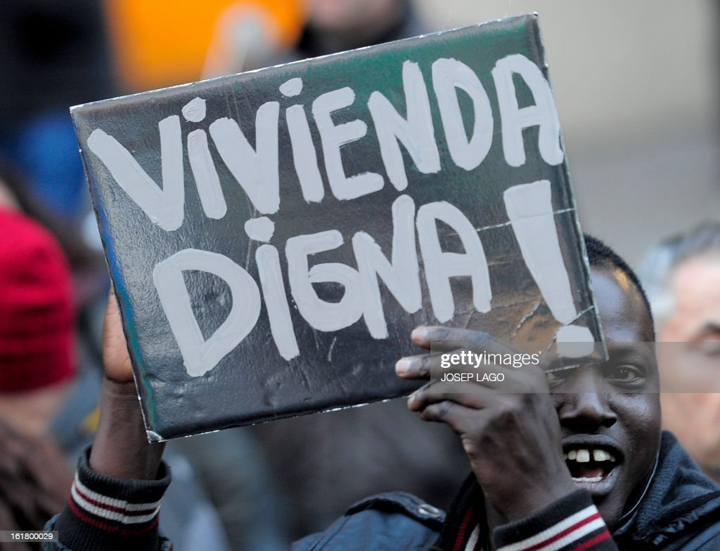 A man holds a placard reading 'Decent housing' during a demonstration called by the organisation Platform for Mortgage Victims (PAH) to push for a new law to end a wave of evictions of homeowners ruined by the economic crisis, on February 16, 2013 in Barcelona. Similar protests were called in 50 other Spanish cities, the latest of months of demonstrations driven by anger at Spain's recession and the conservative government, which is imposing austere economic reforms. Campaigners passed a rare milestone on February 12, 2013 when the Spanish parliament agreed to debate a popular bill of measures to protect poor homeowners, backed by a petition that received more than 1.4 million signatures.