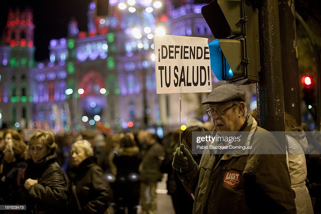 A man holds a placard reading 'Defend your health,' amid other health workers during a demonstration held on the second day of a two-day general strike on November 27, 2012 in Madrid, Spain. For the first time all trade unions called for a 48-hour general health workers strike in the Madrid region after the regional government announced severe cuts and privatization of medical centers.