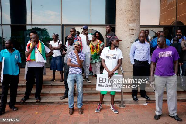 A man holds a placard reading 'Ed for a new Zimbabwe' as people wait for the arrival of Zimbabwe's former vice president and designated president...