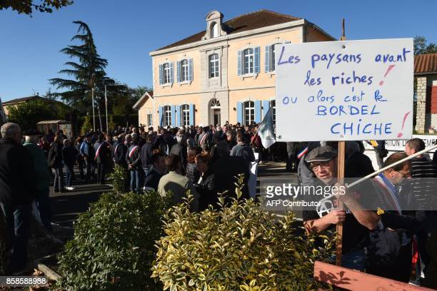 A man holds a placard reading 'Farmers ahead of the rich Or it will be the mess ' during a protest of elected representatives palmiped and poultry...