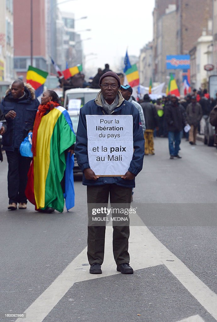 A man holds a placard reading 'For freedom and peace in Mali' during a demonstration, organized by Malian associations, in support of the liberation forces of Mali on January 26, 2013 in Montreuil, near Paris. Placard reads 'For a united Mali, against terrorism'.
