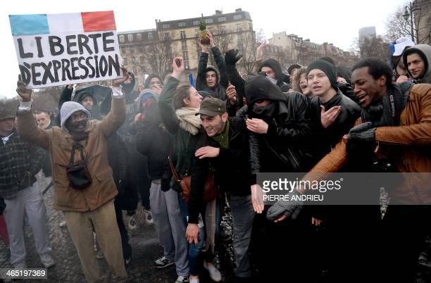 A man holds a placard reading 'Freedom fo speech' as people perform the 'quenelle' gesture popularised by a French controversial comedian during a...