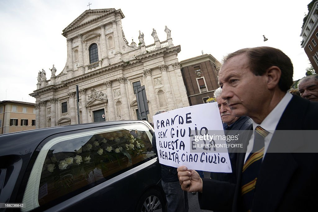 A man holds a placard reading 'Great senator Giulio, this is reality. Goodbye Giulio' as the coffin of seven-time Italian prime minister Giulio Andreotti is carried in a hearse outside the church during the private funeral on May 7, 2013 in Rome. Andreotti, a Machiavellian seven-time Italian prime minister who dominated the political scene for decades, died the day before at the age of 94. AFP PHOTO / FILIPPO MONTEFORTE