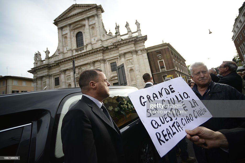 A man holds a placard reading 'Great senator Giulio, this is reality. Goodbye Giulio' as the coffin of seven-time Italian prime minister Giulio Andreotti is carried in a hearse outside the church during the private funeral on May 7, 2013 in Rome. Andreotti, a Machiavellian seven-time Italian prime minister who dominated the political scene for decades, died the day before at the age of 94.