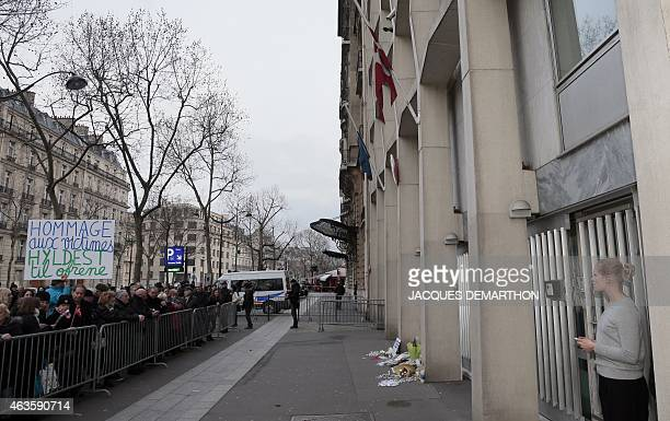 A man holds a placard reading 'Homage to the victims' as people stand outside the Danish Embassy in Paris on February 16 during a commemorative...