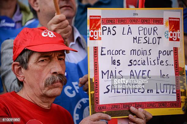 A man holds a placard reading 'I came neither for Meslot nor for the socialists but for the struggling workers' during a demonstration against the...