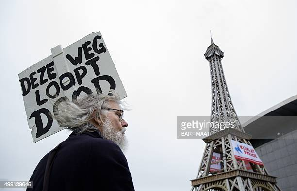 A man holds a placard reading in Dutch 'Deze weg loopt dood' which translates as 'This road is a dead end' on November 29 2015 during a Climate March...