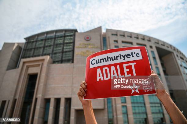 A man holds a placard reading 'Justice for Cumhuriyet' on July 28 2017 during a demonstration in front of Istanbul's courthouse A Turkish court was...