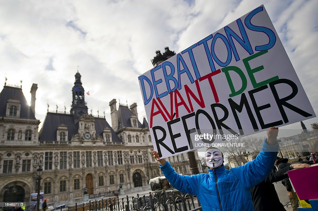 A man holds a placard reading 'Let us debate before reform' during a demonstration against the application for the 2013-2014 schoolyear of a reform law increasing the class time of primary school students in front of Paris' city hall, on March 25, 2013, as Paris' municipal council gathers to vote the law's application.