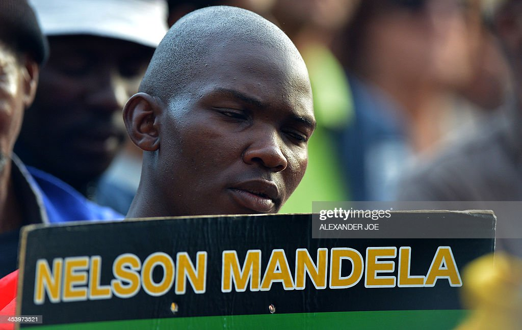 A man holds a placard reading 'Nelson Mandela' while people pray at an ANC party meeting outside the home of South African president Nelson Mandela in Johannesburg on December 6, 2013 where he died the day before. Mandela, the revered icon of the anti-apartheid struggle in South Africa and one of the towering political figures of the 20th century, has died aged 95. Mandela, who was elected South Africa's first black president after spending nearly three decades in prison, had been receiving treatment for a lung infection at his Johannesburg home since September, after three months in hospital in a critical state.