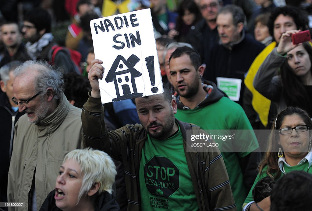 A man holds a placard reading 'No one without a house' during a demonstration called by the organisation Platform for Mortgage Victims (PAH) to push for a new law to end a wave of evictions of homeowners ruined by the economic crisis, on February 16, 2013 in Barcelona. Similar protests were called in 50 other Spanish cities, the latest of months of demonstrations driven by anger at Spain's recession and the conservative government, which is imposing austere economic reforms. Campaigners passed a rare milestone on February 12, 2013 when the Spanish parliament agreed to debate a popular bill of measures to protect poor homeowners, backed by a petition that received more than 1.4 million signatures.