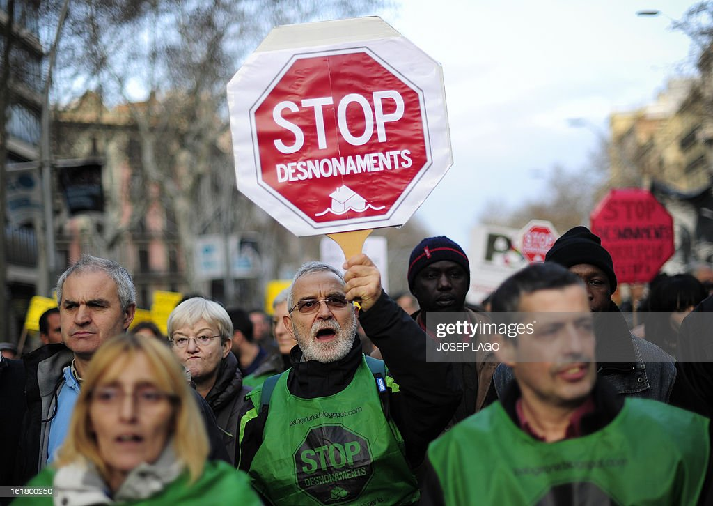 A man holds a placard reading 'Stop evictions' during a demonstration called by the organisation Platform for Mortgage Victims (PAH) to push for a new law to end a wave of evictions of homeowners ruined by the economic crisis, on February 16, 2013 in Barcelona. Similar protests were called in 50 other Spanish cities, the latest of months of demonstrations driven by anger at Spain's recession and the conservative government, which is imposing austere economic reforms. Campaigners passed a rare milestone on February 12, 2013 when the Spanish parliament agreed to debate a popular bill of measures to protect poor homeowners, backed by a petition that received more than 1.4 million signatures. AFP PHOTO/ JOSEP LAGO