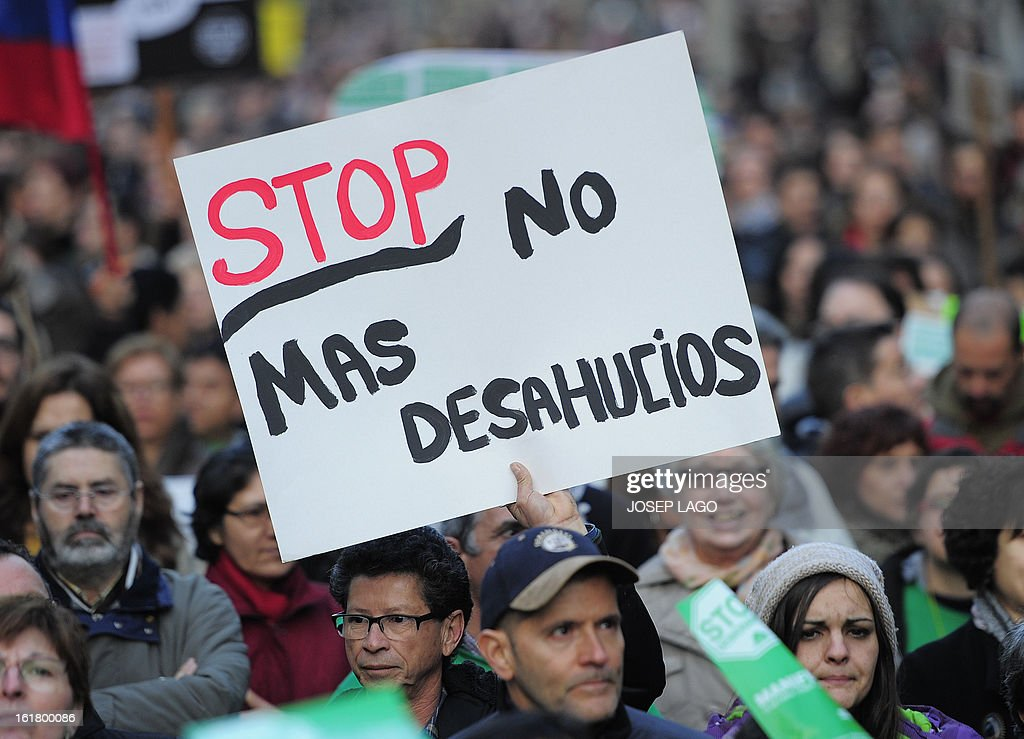 A man holds a placard reading 'Stop no more evictions' during a demonstration called by the organisation Platform for Mortgage Victims (PAH) to push for a new law to end a wave of evictions of homeowners ruined by the economic crisis, on February 16, 2013 in Barcelona. Similar protests were called in 50 other Spanish cities, the latest of months of demonstrations driven by anger at Spain's recession and the conservative government, which is imposing austere economic reforms. Campaigners passed a rare milestone on February 12, 2013 when the Spanish parliament agreed to debate a popular bill of measures to protect poor homeowners, backed by a petition that received more than 1.4 million signatures.