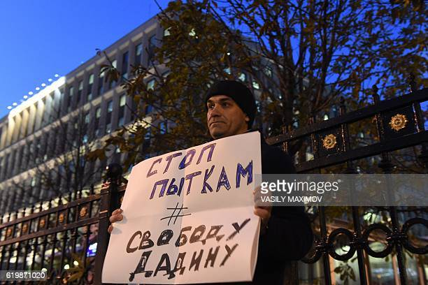 A man holds a placard reading 'Stop torture Freedom for Dadin' as he pickets Russia's Federal Penitentiary Service headquarters in Moscow on November...