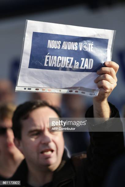 A man holds a placard reading 'We have voted Clear the ZAD' during a demonstration by supporters of the international airport project of...