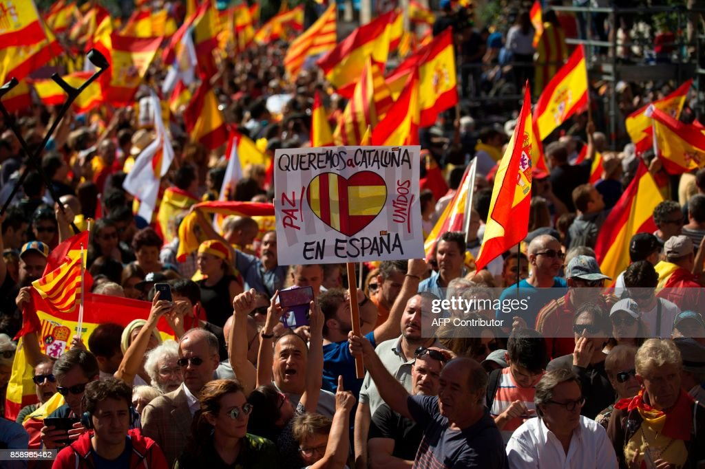 A man holds a placard reading 'We want Catalonia in Spain' during a demonstration called by 'Societat Civil Catalana' (Catalan Civil Society) to support the unity of Spain on October 8, 2017 in Barcelona. Ten of thousands of flag-waving demonstrators packed central Barcelona to rally against plans by separatist leaders to declare Catalonia independent following a banned secession referendum. Catalans calling themselves a 'silent majority' opposed to leaving Spain broke their silence after a week of mounting anxiety over the country's worst political crisis in a generation. GUERRERO