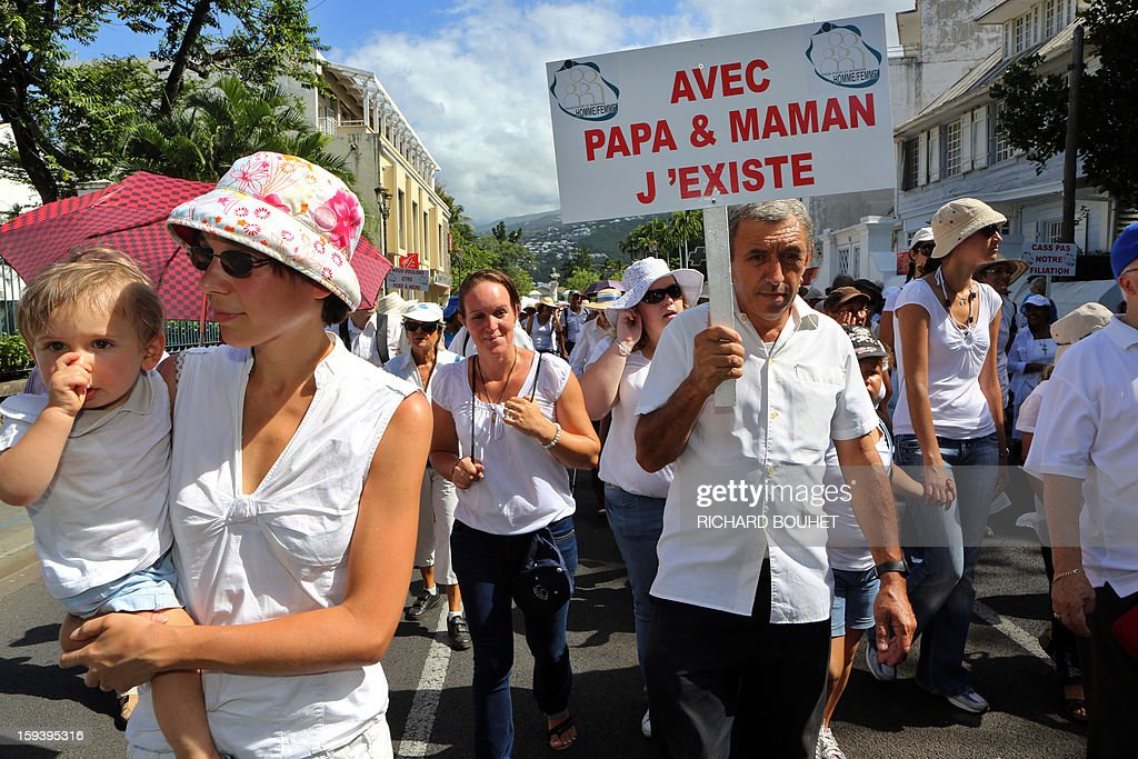 A man holds a placard reading '' with dad and mom, I exist'' during a protest against same-sex marriage, on January 13, 2013 in Saint-Denis de la Reunion, on the French Indian Ocean island of Reunion. Tens of thousands march in Paris on January 13 to denounce government plans to legalise same-sex marriage and adoption which have angered many Catholics and Muslims, France's two main faiths, as well as the right-wing opposition. The French parliament is to debate the bill -- one of the key electoral pledges of Socialist President -- at the end of this month. AFP PHOTO/RICHARD BOUHET