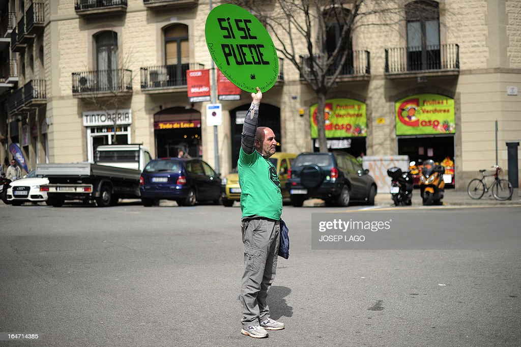 A man holds a placard reading 'Yes we can' during a protest by Platform for Mortgage Victims (PAH) to push for a new law to end a wave of evictions of homeowners ruined by the economic crisis, in Barcelona, on March 27, 2013. AFP PHOTO/ JOSEP LAGO