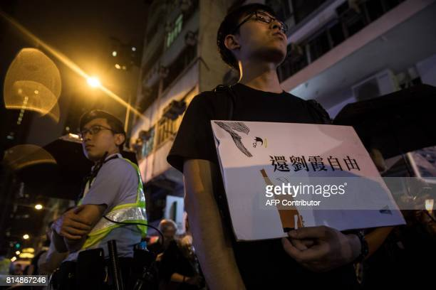 A man holds a placard showing an image of the late Chinese Nobel laureate Liu Xiaobo and his wife Liu Xia with a message reading 'Free Liu Xia'...