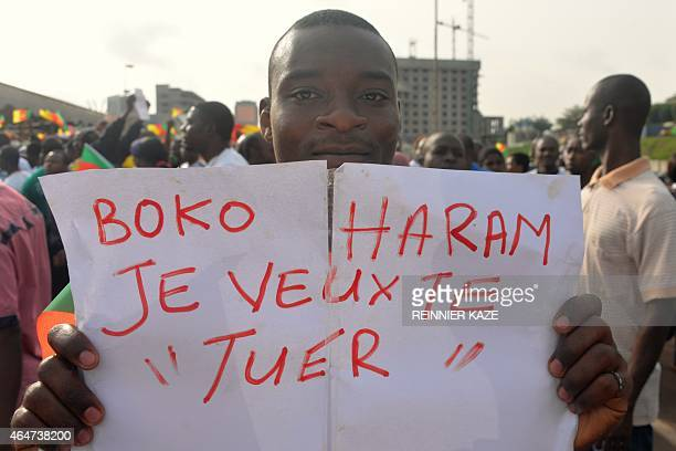 A man holds a placard that reads 'Boko Haram I want to kill you' during a demonstration on February 28 2015 in downtown Yaounde against Islamist...