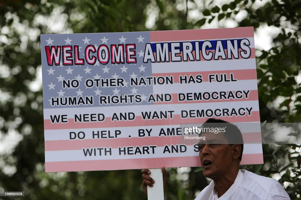 A man holds a placard welcoming the arrival of U.S. President Barack Obama at Yangon International Airport in Yangon, Myanmar, on Monday, Nov. 19, 2012. Obama hailed Myanmar's shift to democracy and urged more steps to increase freedom in the first visit to the former military regime by a U.S. president. Photographer: Dario Pignatelli/Bloomberg via Getty Images