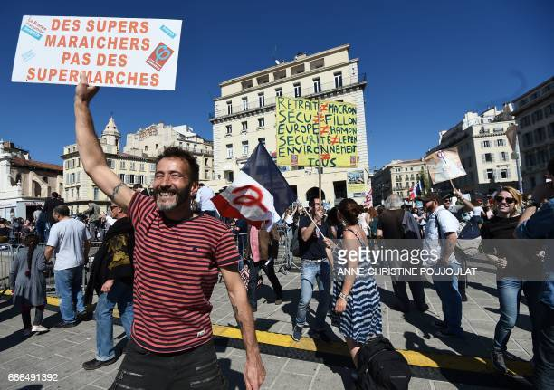 A man holds a placard which translates as 'Super market gardener not supermarket' as a woman holds a French national flag with the letter 'phi' the...